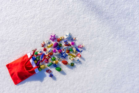 Red bag with many colorful new year toys lying on white fresh snow. Santa Claus scattered bag of gifts. Merry Christmas and Happy New Year. Greeting card for winter holidays. Top view, copy space.