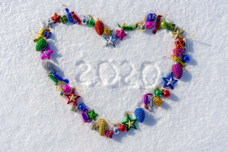 Heart symbol made of many colorful christmas or new year toys and text 2020 on white fresh snow in sunny winter day. Merry Christmas and Happy New Year. Winter holidays concept. Top view, copy space.