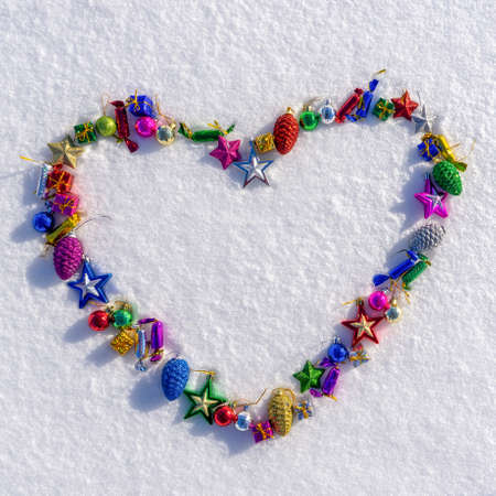 Heart symbol made of many colorful christmas or new year toys lying on white fresh snow in sunny winter day. Merry Christmas and Happy New Year. Winter holidays concept. Top view, copy space.