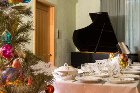 Living room interior with beautiful decorated Christmas tree, festive table and vintage piano. Concept of new year holiday at cozy home. 스톡 콘텐츠
