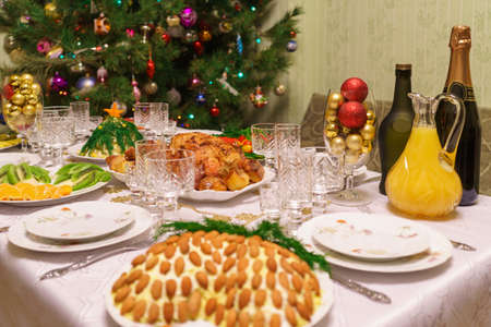 Served table with festive dishes near beautiful decorated Christmas tree in living room interior. Concept of new year holiday at cozy home. 스톡 콘텐츠
