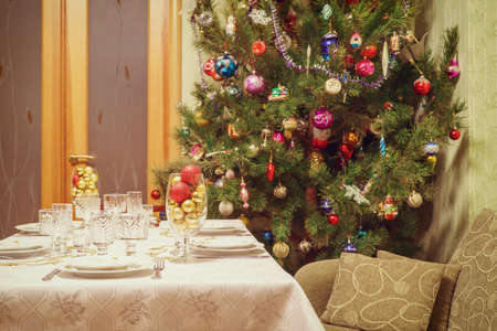 Beautiful decorated Christmas tree and festive table in living room interior with sofa and door. Concept of new year holiday at cozy home. Vintage tone.
