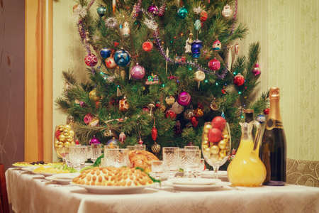Served table with festive dishes near beautiful decorated Christmas tree in living room interior. Concept of new year holiday at cozy home. Focus on fir, vintage tone.