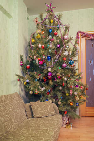 Beautiful big decorated Christmas tree with many multi colored toys in living room interior. Concept of new year holiday at cozy home. Vintage tone. 스톡 콘텐츠