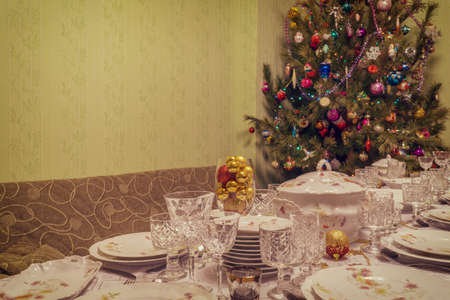 Served table with festive tableware near beautiful decorated Christmas tree in living room interior. Concept of new year holiday at cozy home. Vintage tone. 스톡 콘텐츠
