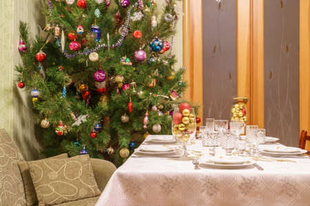 Beautiful decorated Christmas tree and festive table in living room interior with sofa and door. Concept of new year holiday at cozy home.