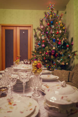 Served table with festive tableware near beautiful decorated Christmas tree in living room interior. Concept of new year holiday at cozy home. Selective focus, vintage tone.