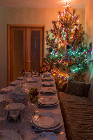 Served table with festive tableware near beautiful decorated Christmas tree in living room interior. Concept of new year holiday at cozy home.
