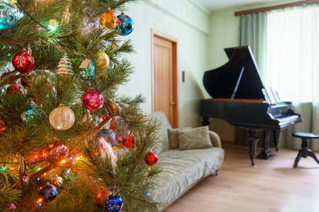 Beautiful festive decorated Christmas tree in living room interior with sofa, piano and window. Concept of new year holiday at cozy home.