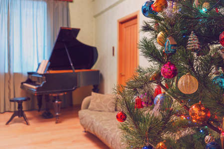 Beautiful festive decorated Christmas tree in living room interior with sofa, piano and window. Concept of new year holiday at cozy home. Vintage tone. 스톡 콘텐츠