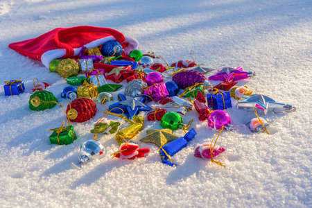 Red bag with many colorful new year toys and decorative items lying on white fresh snow. Santa Claus scattered bag of gifts. Merry Christmas and Happy New Year. Greeting card for winter holidays. Stockfoto - 133692132