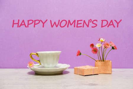 夏天创造性静物在最小的风格。桃红色玛格丽特雏菊在小礼物盒的花花束有白色咖啡杯的在轻的淡紫色背景