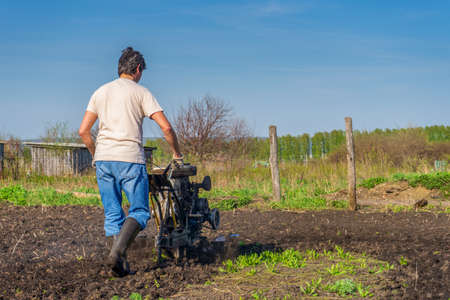 Man in wellingtons with cultivator ploughing ground in sunny day. Farmer plowing kitchen-garden in suburb. Land cultivation, soil tillage. Spring work in garden. Gardening concept. Stock fotó