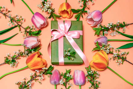Round frame made of colorful pink and orange tulips with cherry blossom twigs on peachy background and gift box wrapping in green paper with pink ribbon. Beautiful spring floral greeting card. Stock fotó