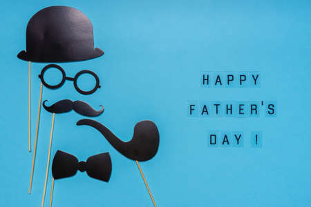 Various black photo booth props: cylinder hat, glasses, moustache, smoking pipe, bow tie on blue background. Greeting card, text HAPPY FATHER'S DAY. Creative composition in minimal style. Stock fotó