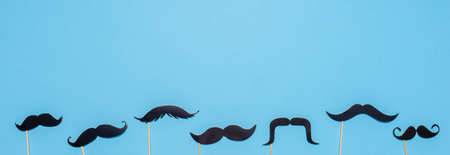 Various black photo booth props moustaches of different shape on blue background. Greeting card for father's day or men's health awareness month campaign concept. Flat lay, banner.