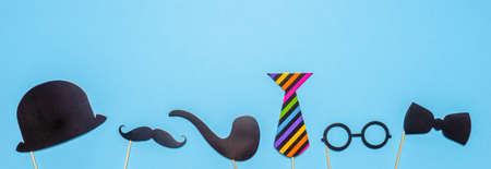 Various black photo booth props: cylinder hat, glasses, moustache, smoking pipe, bow tie on blue background. Greeting card for father's day, masculinity concept. Flat lay, copy space, mock up, banner.