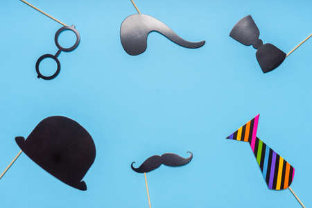 Various black photo booth props: cylinder hat, glasses, moustache, smoking pipe, bow tie on blue background. Greeting card for father's day, masculinity concept. Flat lay, copy space, mock up.