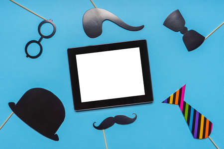 Various black photo booth props and empty tablet screen on blue background. Greeting card for father's day, masculinity concept. Flat lay, copy space, mock up.