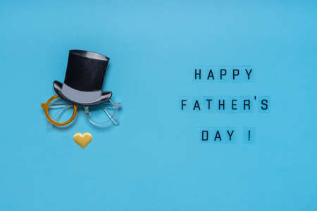 Photo booth props cylinder hat, glasses and nose of heart shape on blue background. Greeting card, text HAPPY FATHER'S DAY. Creative composition in minimal style.