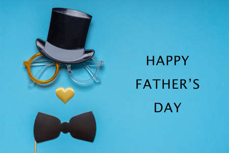 Various black photo booth props: cylinder hat, glasses, bow tie and nose in heart shape on blue background. Greeting card for father's day. Creative composition in minimal style, space for text.