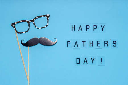 Photo booth props moustache and glasses on blue background. Text HAPPY FATHER'S DAY, greeting card in minimal style. Flat lay.