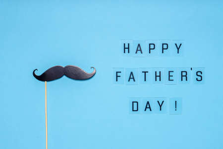 Photo booth props moustache on blue background. Text HAPPY FATHER'S DAY, greeting card in minimal style. Flat lay. Stock fotó