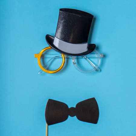 Black photo booth props: cylinder hat, glasses and bow tie on blue background. Greeting card for father's day. Creative composition in minimal style, flat lay, top view.