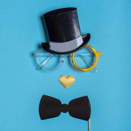 Various black photo booth props: cylinder hat, glasses, bow tie and nose in heart shape on blue background. Greeting card for father's day. Creative composition in minimal style. Stock fotó