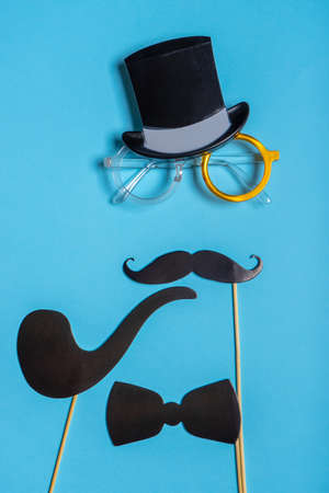 Various black photo booth props: cylinder hat, glasses, moustache, smoking pipe, bow tie on blue background. Greeting card for father's day. Creative composition in minimal style.