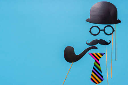 Various black photo booth props: cylinder hat, glasses, moustache, smoking pipe, bow tie on blue background. Greeting card for father's day, masculinity concept. Creative composition, space for text.