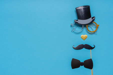 Various black photo booth props: cylinder hat, glasses, moustache, bow tie and nose in heart shape on blue background. Greeting card for father's day. Creative composition, space for text.