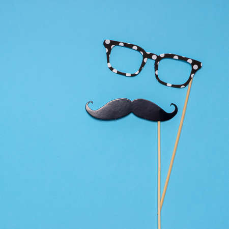 Photo booth props moustache and glasses on blue background. Greeting card for father's day or men's health awareness month campaign concept. Flat lay, space for text. Stock fotó
