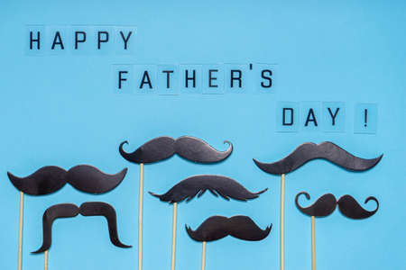 Various black photo booth props moustaches of different shape on blue background. Greeting card, text HAPPY FATHER'S DAY. Flat lay, top view.