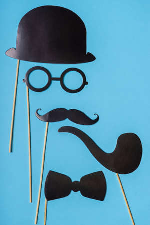 Various black photo booth props: cylinder hat, glasses, moustache, smoking pipe, bow tie on blue background. Greeting card for father's day, masculinity concept. Creative composition in minimal style.