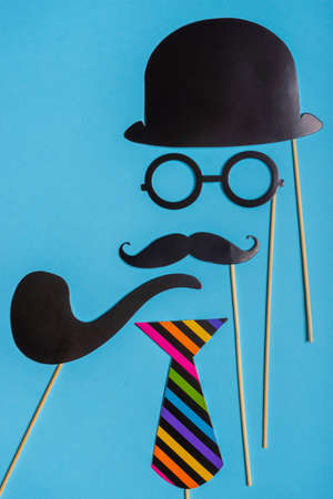 Various black photo booth props: cylinder hat, glasses, moustache, smoking pipe, tie on blue background. Greeting card for father's day, masculinity concept. Creative composition in minimal style. Stock fotó