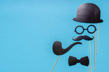 Various black photo booth props: cylinder hat, glasses, moustache, smoking pipe, bow tie on blue background. Greeting card for father's day. Creative composition in minimal style, space for text. Stock fotó