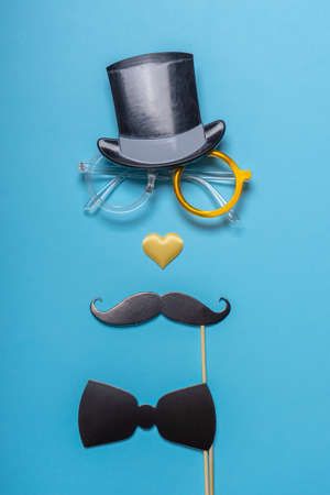 Various black photo booth props: cylinder hat, glasses, moustache, bow tie and nose in heart shape on blue background. Greeting card for father's day. Creative composition in minimal style.