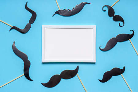 Various black photo booth props moustaches and white empty photoframe on blue background. Greeting card for father's day or men's health awareness month campaign concept. Flat lay, copy space mock up