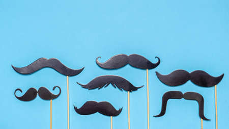 Various black photo booth props moustaches of different shape on blue background. Greeting card for father's day or men's health awareness month campaign concept. Flat lay, space for text, mock up.