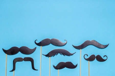Various black photo booth props mustaches of different shape on blue background. Greeting card for father's day or men's health awareness month campaign concept. Flat lay, space for text, mock up.