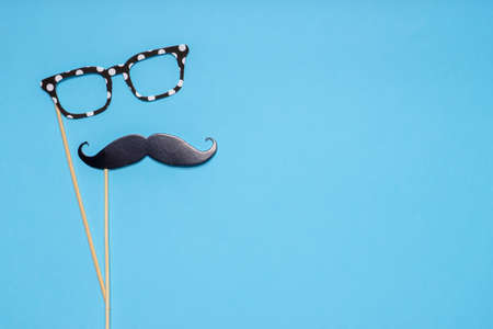 Photo booth props mustache and glasses on blue background. Greeting card for father's day or men's health awareness month campaign concept. Flat lay, space for text. Standard-Bild