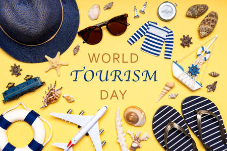 Happy world tourism day. Touristic clothes, hat, flip-flops, sunglasses and decorative items on light pastel background. Flat lay, top view. Creative composition with text WORLD TOURISM DAY. Standard-Bild