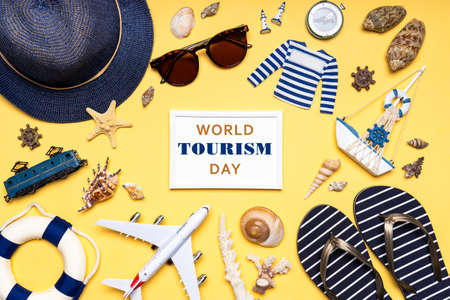 Happy world tourism day. Touristic clothes, hat, flip-flops, sunglasses and decorative items on light pastel background. Flat lay, top view. White photo frame with text WORLD TOURISM DAY.