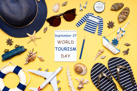 Happy world tourism day. Touristic clothes, hat, flip-flops, sunglasses and decorative items on light pastel background. Flat lay, top view. Notebook with text September 27 WORLD TOURISM DAY. Standard-Bild
