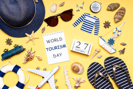 Happy world tourism day. Touristic clothes, hat, flip-flops, sunglasses and decorative items on light background. Flat lay, top view. Calendar date 27 September, notebook with text WORLD TOURISM DAY. Standard-Bild