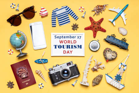 Happy world tourism day. Touristic objects, smartphone, passport, camera, sunglasses and decorative items on light background. Flat lay, top view. Photoframe, text September 27 WORLD TOURISM DAY Standard-Bild