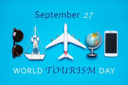 Happy world tourism day. Touristic objects, smart phone, sunglasses, globe and decorative airplane and vessel on blue background. Flat lay, top view. Text September 27, WORLD TOURISM DAY.