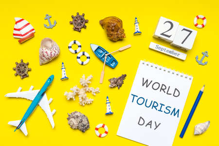 Happy world tourism day. Touristic decorative items, plane, vessel, seashells on bright yellow background. Flat lay, top view. Calendar date September 27, notebook with text WORLD TOURISM DAY. Standard-Bild