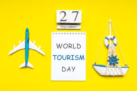 Happy world tourism day. Touristic decorative items, plane and vessel on bright yellow background. Flat lay, top view. Calendar date September 27, notebook with text WORLD TOURISM DAY.